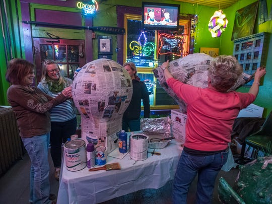 """People gather at the Up Over Bar in Covington on Feb. 6 to create """"big heads"""" to wear for the Covington Mardi Gras Grande Parade on Feb. 25."""