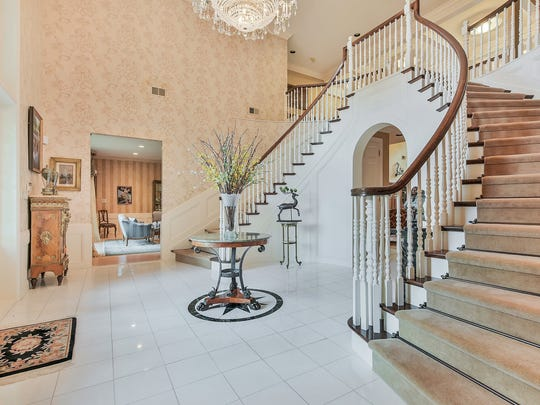 The foyer has marble floors, a crystal chandelier and