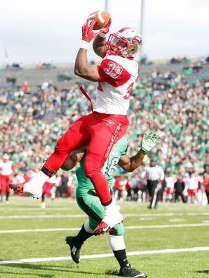 Nov 28, 2014; Huntington, WV, USA; Western Kentucky Hiltoppers running back Leon Allen (33) scores a touchdown against Marshall Thundering Herd linebacker Jermaine Holmes (46) during the first half at Joan C. Edwards Stadium. Mandatory Credit: Mark Zerof-USA TODAY Sports