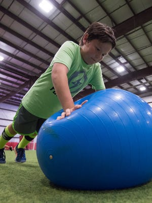 Aidan Quintana (10) completes push-ups using a ball during a training session with Sports Specific Training at Slim's Sports Complex in Middletown.