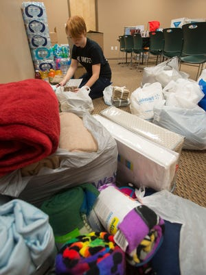 (File photo) United Way employee, Sarah St. Ores, sorts donated items by classification before being taken to the tornado victims relief store at the organization's Government Street offices March 6, 2016.
