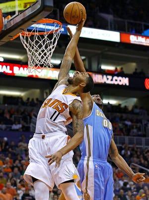 Phoenix Suns forward Markieff Morris tries to score on a rebound against Denver Nuggets forward Darrell Arthur (during the first half on Wednesday, Nov. 26, 2014. in Phoenix.