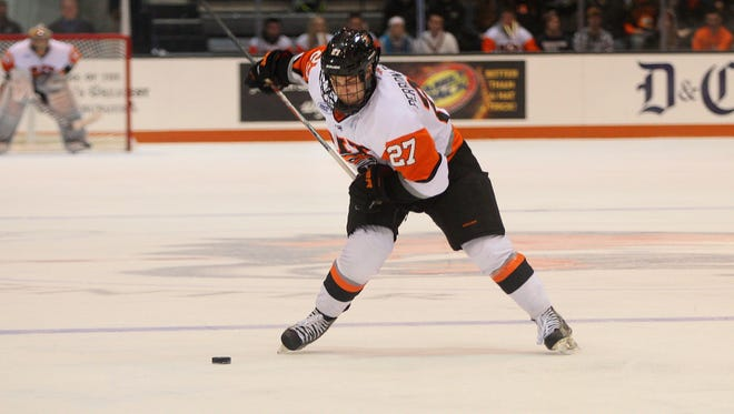 RIT men's hockey player Alex Perron-Fontaine takes a shot in a game earlier this season. RIT is pushing for a change in NCAA rules so it can offer scholarships to its Division I athletes.