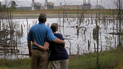Bryant Gobble, left, hugs his wife, Sherry Gobble, right, as they look from their yard across an ash pond full of dead trees toward Duke Energy's Buck Steam Station in Dukeville. Duke says it will provide bottled water to residents living near coal ash pits in North Carolina. So far, more than 150 residential wells tested near Duke's dumps have failed to meet state groundwater standards.
