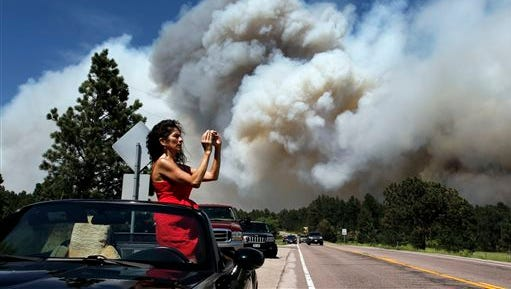 FILE - In this June 12, 2013 file photo, Colorado Springs resident Yolette Baca takes a photo of the wildfire in the Black Forest area north of Colorado Springs, Colo.The leaders of the Interior and Agriculture departments discussed the nationwide outlook for the 2015 wildfire season in a conference call from Denver on Tuesday, June 8, 2015. Interior Secretary Sally Jewell and Agriculture Secretary Tom Vilsack reviewed the risk of catastrophic wildfires, especially in the West. (AP Photo/Brennan Linsley, file)