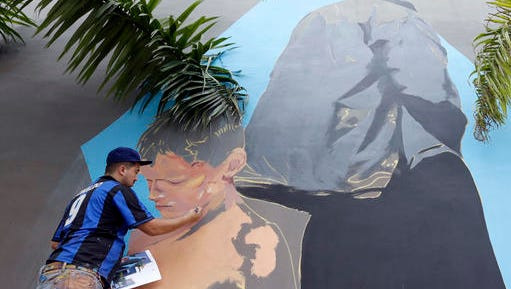 Artist Cazdos, of Colombia, works on a mural, Friday, Dec. 2, 2016, in the Wynwood Art District in Miami, as the annual Art Basel festival continues, featuring poolside parties, blocks of art fairs and outdoor red carpet events. This marks the 15th year that Art Basel has been held in the Miami area.