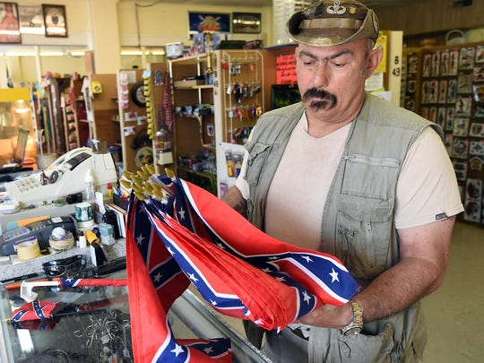 David Alvirez, owner of PGW Collectibles in Lakeview, looks through a shipment of Confederate flags on Monday. Alvirez said the national controversy concerning the flag has been good for business.