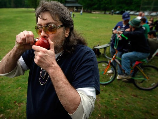 "Thorne ""The Kingpin"" Peters smokes marijuana out of an apple as a small group of marijuana legalization advocates gathered at Overton Park for the annual observance of 4/20, the counterculture holiday derived from ""420"" - insider shorthand for cannabis consumption."