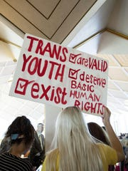 Hunter Schafer, of Raleigh, holds a sign in favor of repealing North Carolina HB2 during a special session of the North Carolina General Assembly in Raleigh, N.C., Wednesday, Dec. 21, 2016.