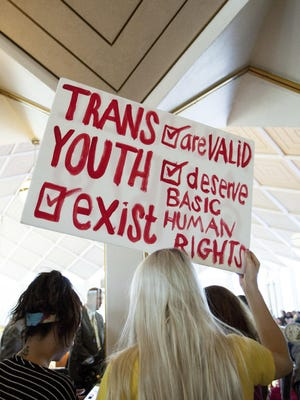 Hunter Schafer, of Raleigh, holds a sign in favor of repealing North Carolina HB2 during a special session of the North Carolina General Assembly in Raleigh, N.C., Wednesday, Dec. 21, 2016. North Carolina's legislature is reconvening to see if enough lawmakers are willing to repeal the 9-month-old law that limited LGBT rights, including which bathrooms transgender people can use in public schools and government buildings.(AP Photo/Ben McKeown)