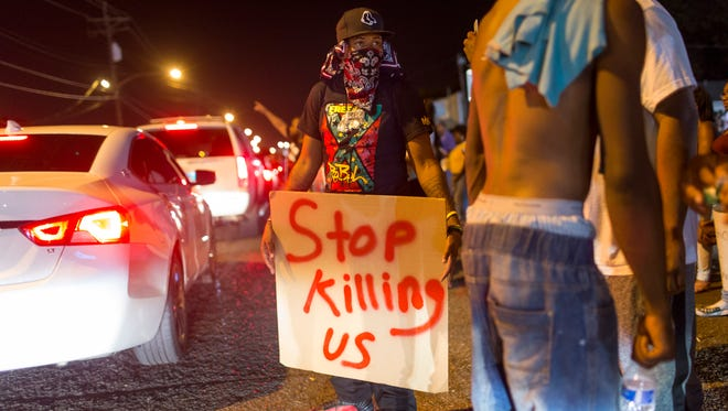 Protesters try to catch the attention of passing drivers after a vigil for Alton Sterling, near the convenience store where the 37-year-old was shot dead while being taken into police custody, in Baton Rouge, La. July 6, 2016.