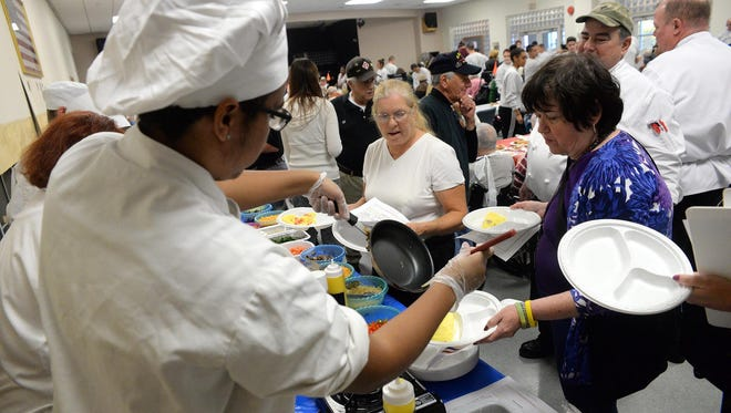 Kayvaughn Montijo, 17, of Atlantic City (left), gives an omelet to volunteer Marie Gittone, of Vineland (right), who will serve it to a resident at New Jersey Veterans Memorial Home during Veterans Day brunch, Sunday, Nov. 8.