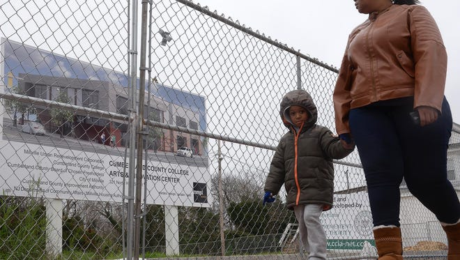 Millville residents Danayia McManamy and her son Meki McManamy, 4, walk past the site of the Cumberland County College Arts and Innovation Center in Millville, where a fence was erected Wednesday.  Construction is to begin next week.