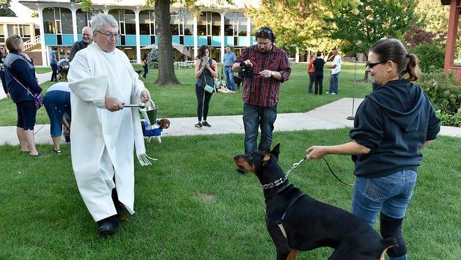 The Rev. Charles Morris blesses Noble and probably owner Ann Stacherski, too.