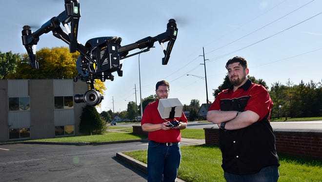 Fred and Alex Kandah, flying a drone in the parking lot of their business.