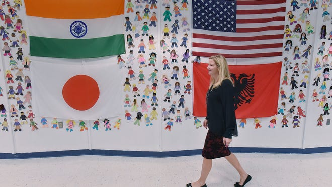 Principal April Quasarano walks through the cafeteria. The International Cafe's walls reflect the diversity of students at Dodson Elementary.