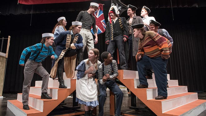 The cast includes, foreground; Molly (Amber Killingbeck), Peter Pan (Chandler Motley), on risers from left; Prentiss (Juliet Metivier), Fighting Prawn (Brianna Fuchs), Captain Scott (Jenna Wiehe), Bill Slank (Logan Kilbury), Black Stash (Marianna Seal), Smee (Tony Kelly), Alf (Megan Coon), Mrs. Bumbrake (Logan Wallace), and Lord Leonard Aster (Wiley Strasser).