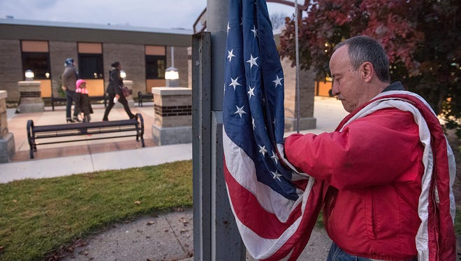 Voters walk into the polls while Dale Yanka prepares to hoist the flag, as election day begins at Kennedy Elementary in Livonia.