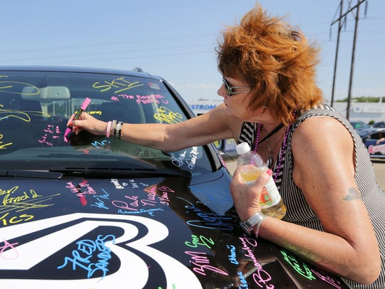 Shirley Wunderlich signs a car Saturday in honor of