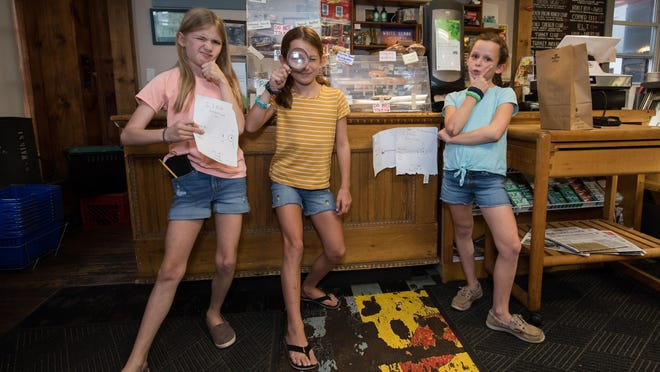 The Little Detictives Co. pose for a photo next to their advertisement inside the Newfields Country Store.