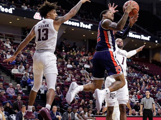 Auburn guard Bryce Brown (2) shoots between Texas A&M guard Brandon Mahan (13) and guard Savion Flagg (1) during the first half of an NCAA college basketball game, Wednesday, Jan. 16, 2019, in College Station, Texas. (AP Photo/Michael Wyke)