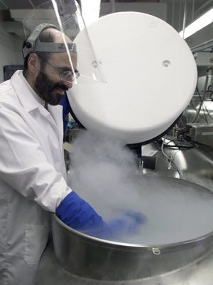 Jay Tischfield, head of a genetics lab at Rutgers, looks into one of several tanks cooled by liquid nitrogen where genetic material of more than 20,000 people is stored.