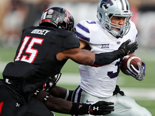 Kansas State running back Dalvin Warmack tries to get away from Texas Tech defensive back Vaughnte Dorsey in the second quarter during an NCAA college football game Saturday, Nov. 4, 2017, in Lubbock, Texas. (Mark Rogers/Lubbock Avalanche-Journal via AP)