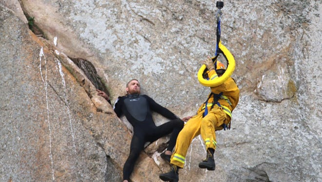 In this photo provided by Bob Isenberg, Michael Banks is stranded on a ledge some 80 feet off the ground on Morro Rock, a landmark in Morro Bay, Calif., Thursday, April 7, 2016. He had scaled the rock to make an Internet proposal to his girlfriend - who said yes - but then got stuck on a ledge and couldn't get down. A helicopter had to be called, and Morro Bay Fire Department Capt. Todd Gailey was lowered by cable to pluck Banks and take him to safety.