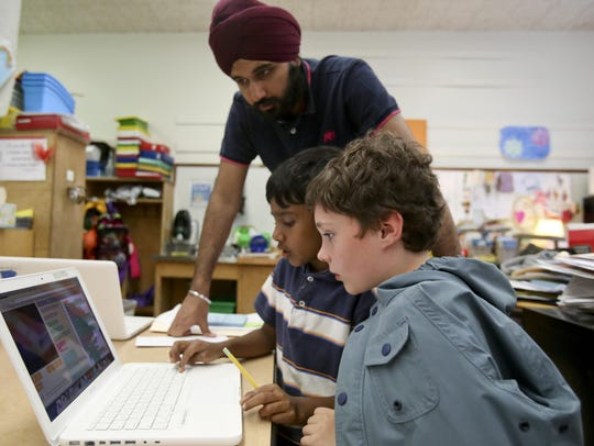 Cornell University graduate Arjan Nirh watches as second-graders