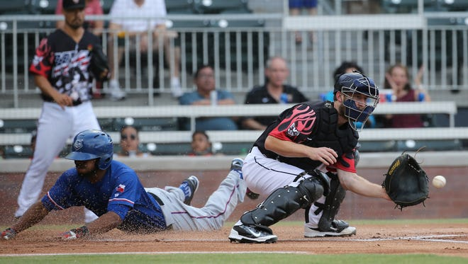 El Paso catcher Rocky Gale waits for the throw as Round Rock's Delino DeShields slides into home safe.