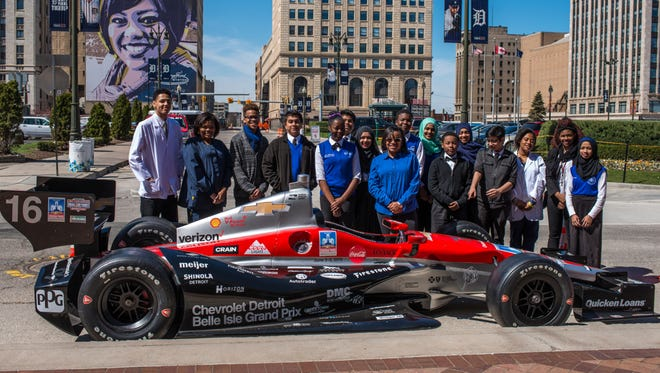 Students from Ben Carson High School in Detroit with the Grand Prix IndyCar before a Detroit Medical Center event at Comerica Park in April.
