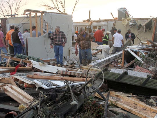 """People inspect a storm-damaged home in the Roundaway community near Clarksdale, Miss., Wednesday, Dec. 23, 2015. A storm system forecasters called """"particularly dangerous"""" killed multiple people as it swept across the country Wednesday."""