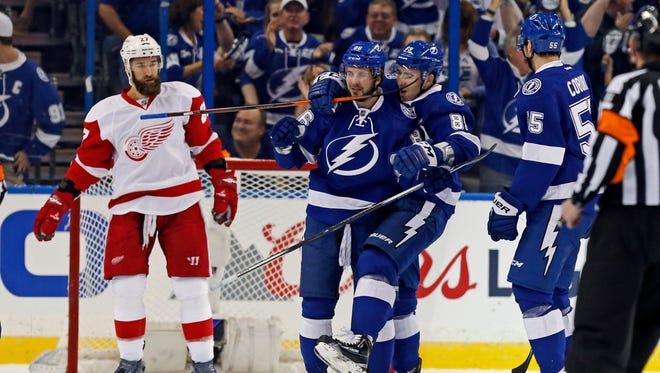 The Lightning's Nikita Kucherov is congratulated on his goal by teammates Nikita Nesterov, center, and and Jason Garrison as Red Wings defenseman Kyle Quincey reacts during the first period in Game 1 of Game 1 of the Eastern Conference quarterfinals Wednesday in Tampa, Fla.