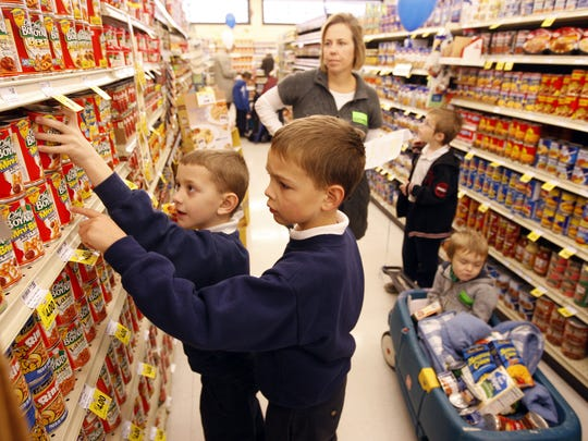 Thomas McCoy (left) and Ben Sweeten, students at Blessed Sacrament School select canned goods to buy at the Fort Mitchell Remke Market. This location will be the fourth Remke to close since 2015.