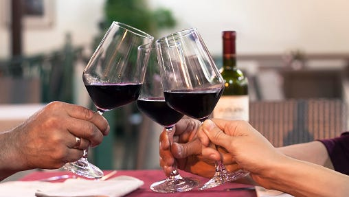 Group of friend clinking glasses of wine in a restaurant