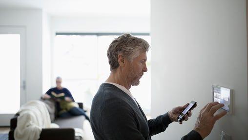Senior man using smart phone app, adjusting digital thermostat