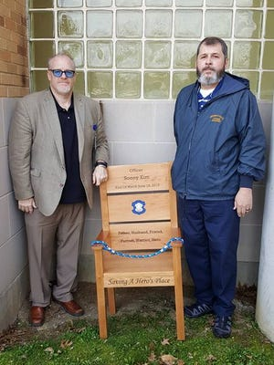 John Keuffer, left, and Mark Wooten recently delivered an honor chair to Cincinnati police District 2. The chair is a memorial to Sonny Kim, who was killed in the line of duty in 2015.
