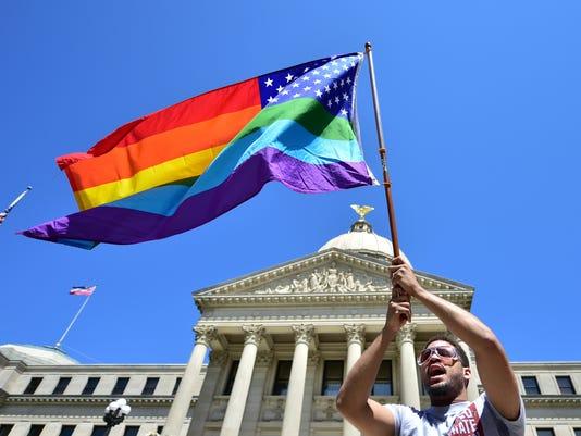 House Bill 1523 protester holds rainbow flag.