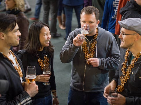 A group of attendees samples brews with pretzel necklaces to clear their palates.