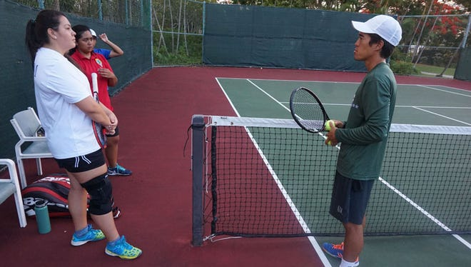 Guam national tennis team coach Chas Okamoto, right, works with national team players, from left, Camdyn Nadler and Charlayne Espinosa, during a practice at the Hyatt Regency Guam courts. The men's team will be Joshua Cepeda and Andrew Chung.