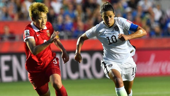 China's Pang Fengyue (L) vies for the ball with US player Carli Lloyd during a 2015 FIFA Women's World Cup quarterfinal match between the US and China at Lansdowne Stadium in Ottawa, Ontario on June 26, 2015.    AFP PHOTO/ NICHOLAS KAMMNICHOLAS KAMM/AFP/Getty Images