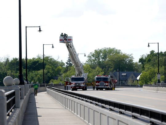 Firefighters work along College Avenue to access the roof of a building on the 200 block of South Riverheath Tuesday, May 24, 2016 in Appleton.