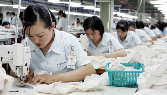 File photo shows North Koreans at work at a factory of South Korean apparel maker Shinwon company in the inter-Korean industrial park in Kaesong, North Korea, in April.