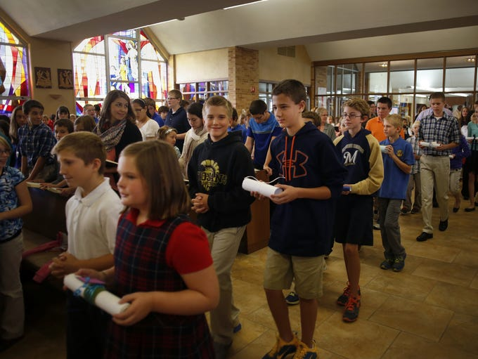 Students carry scrolls into the all-school Mass at St. Gabriel the Archangel Parish on Wednesday, October 1, 2014, in Neenah, Wis. The scrolls, each from a different school, were then traded around. The scrolls contain prayers for each school. Nearly 600 and faculty from Catholic schools in the Diocese of Green Bay participated in the mass. Bishop David L. Ricken was the celebrant of the Mass.