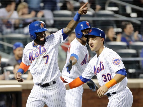 New York Mets' Jose Reyes (7) celebrates with teammate Michael Conforto (30) as he gestures to teammate Wilmer Flores after scoring on a Flores double during the third inning of a baseball game against the San Diego Padres, Wednesday, May 24, 2017, in New York.