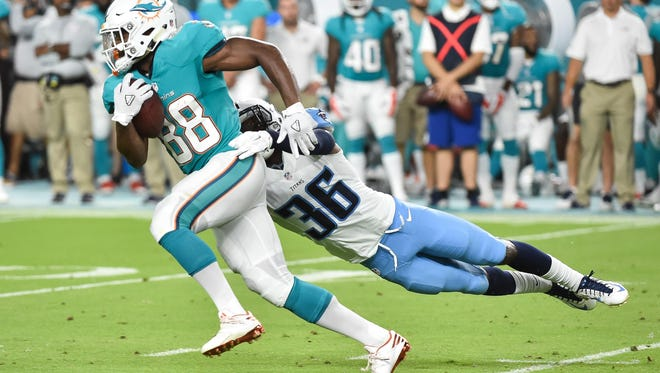 Dolphins wide receiver Leonte Carroo (88) is tackled by Titans wide receiver Andrew Turzilli (86) during the first half Thursday.