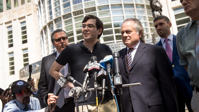 """This file photo taken in 2017 shows so-called """"Pharma bro"""" Martin Shkreli, center, outside Brooklyn federal court in New York City after he was convicted on three of eight criminal charges against him in a securities fraud case."""