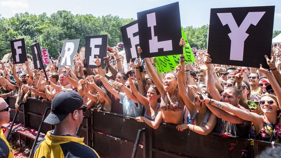 """Fans hold up a """"Firefly"""" set of signs as Steve Aoki performs on The Backyard stage at Firefly in 2015."""