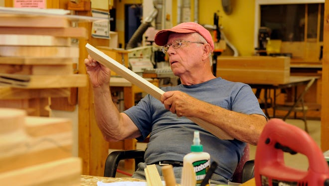 """Mel Strack works on building """"little free libraries,"""" which are posted around neighborhoods in the St. Cloud area. He builds them at his work space in the wood shop at the Whitney Senior Center."""