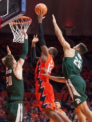 Illinois forward Leron Black (12) shoots while defended by Michigan State guard Matt McQuaid (20) and forward Kenny Goins (25) during the first half on Monday, Jan. 22, 2018, in Champaign, Ill.